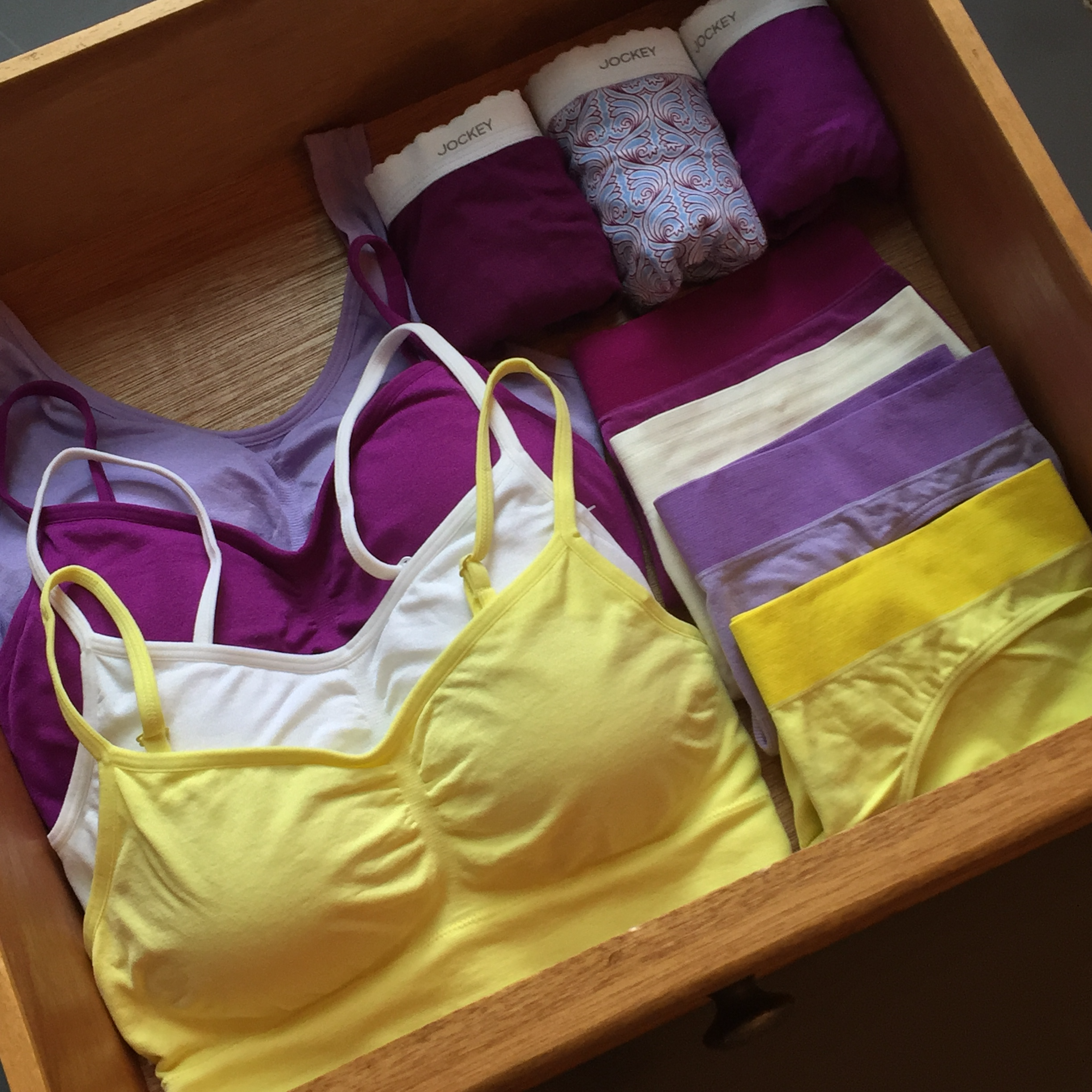 Sports bras and Womens underwear folded in a drawer.