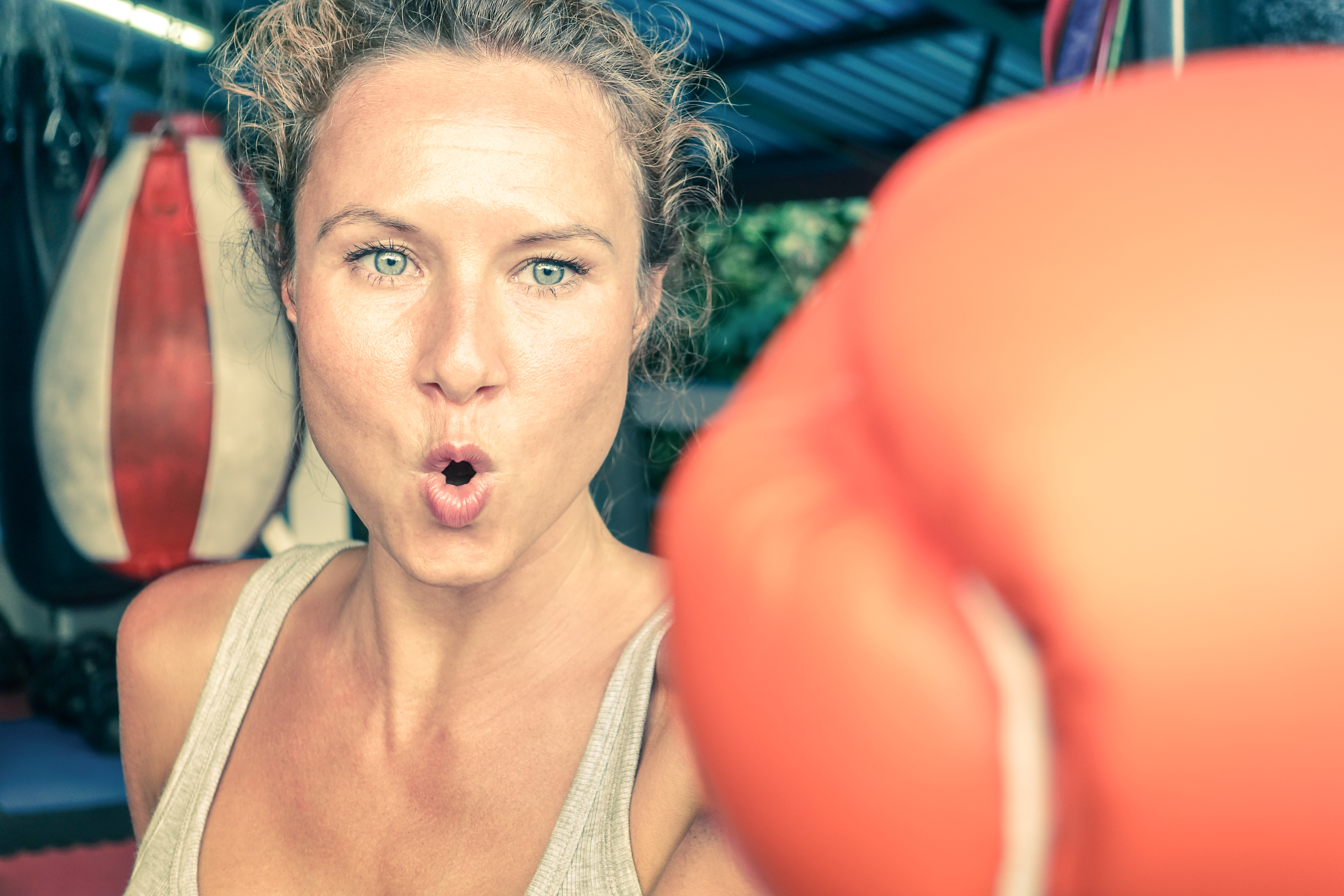 Woman hitting with punch on gritty determination at fitness boxing