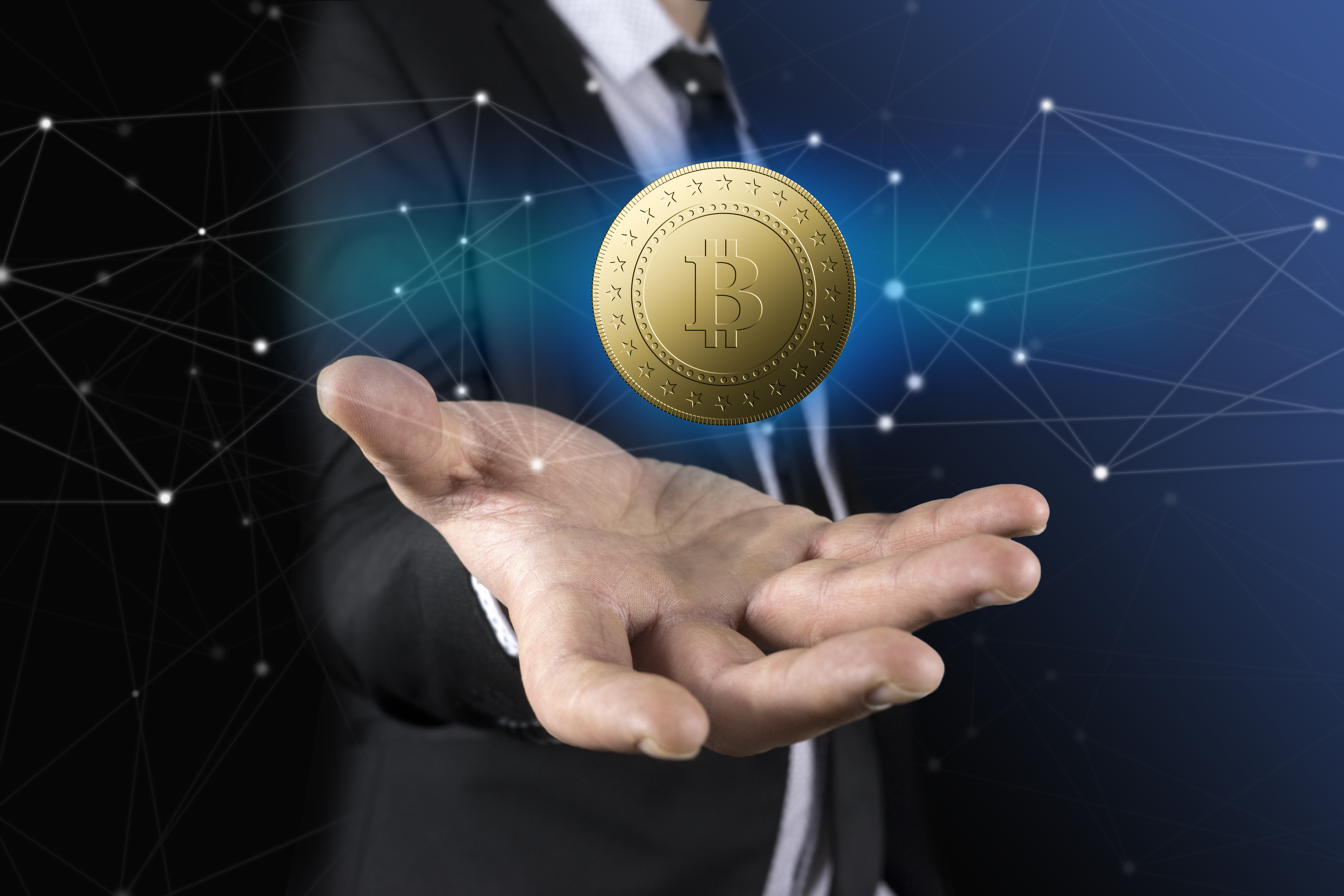Business man with black suit holding bitcoin on hand