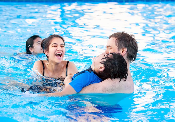 Family playing and exercising in swimming pool